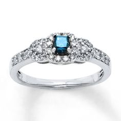 """A princess-cut blue diamond, framed by sparkling round white diamonds, creates an engagement ring that will forever be your """"something blue."""""""