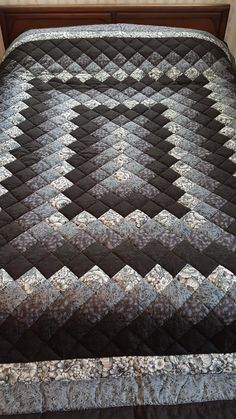 This stunning black and gray hand-quilted Trip Around the World quilt is Queen Size. The fabrics include a variety of swirls, florals and more