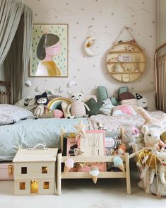 A little girl's room with Hibou Home wallpaper and bedding, Ikea book storage, Olli Ella holdie house, Liberty bedding by Coco&Wolf to create a warm, cosy pastel space. Garlands by Velveteen Babies