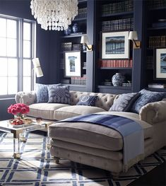 Navy walls & built-ins, lucite & brass coffee table, chandelier, #brass #lucite #navy. Love the coffee table