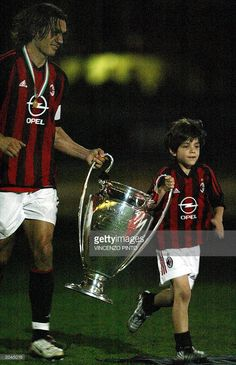 AC Milan captain Paolo Maldini and his son Crhistian (R) carry the Champions League cup, won in the final match against Juventus at the Old Trafford stadium in Manchester on May 28, at the end of the second leg of the final match of the Italy Cup against AS Roma at Milan's Meazza stadium 31 May 2003. AS Roma won the match 2-1 as AC Milan took the last Italian trophy.