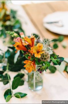 Simple, rustic wedding centerpiece idea - orange flower + greenery centerpiece - See more from this rustic wedding on WeddingWire! {Picturist Photography}