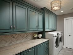 Laundry room with glazed robin's egg blue cabinet. Barrington Homes Inc.
