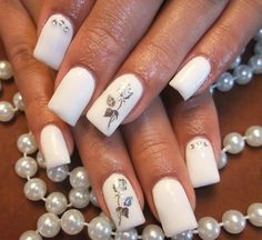Elegant white rose nail art design. The nails have been painted in white nail polish, and the roses added on top in silver nail polish which simply look stunning.