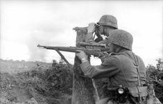 Eastern Front, Voronezh sector, June 1942: Sniper and spotter take position. Note the helmet camouflage covers. They are of dissimilar pattern and fit like a glove (no leather band to hold them into place). Note also the flashlight hanging from the belt of the sniper -- standard issue to all foot soldiers. The rifle is the classic 98 with a scope added.