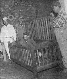 """A patient being locked away in the """"Utica Crib,"""" a primitive treatment that confined mentally ill people who posed a physical danger to others at the Utica Insane Asylum. The Crib was criticized for being inhumane, but widely used for nearly 100 years."""