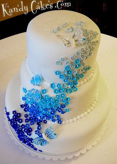 White wedding cake with blue ombré flowers and butterflies    Keywords: #royalblueweddings #jevelweddingplanning Follow Us: www.jevelweddingplanning.com  www.facebook.com/jevelweddingplanning/