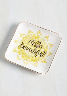 When your rings, bracelets, and brooches say good morning from this flattering jewelry tray, it's impossible to have a glum start to your day! Made of white ceramic and starring a patterned sun, a sweet phrase, and a metallic gold rim, this cute dresser accessory brings positivity to your every day.