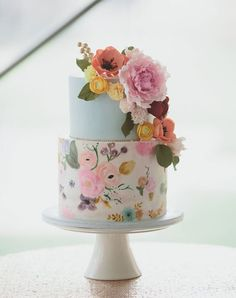 Whoever said you had to walk down the aisle with a traditional bouquet? We love this bright floral watercolor wedding cake.