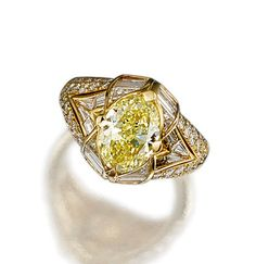 FANCY INTENSE YELLOW DIAMOND AND DIAMOND RING, BULGARI.  Set at the centre with an oval fancy intense yellow diamond weighing 3.01 carats, within baguette, calibré- and brilliant-cut diamond surrounds, mounted in yellow gold,  signed Bulgari and numbered, maker's marks