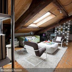 An ein Landhaus erinnert dieses Dachzimmer mit Holzverkleidung an der Decke und rustikalen Dielen. Die heimelige Atmosphäre wird durch die Gestaltung mit Holz…