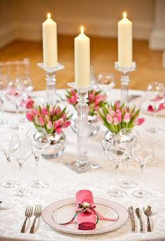 kleine rosa Tulpen in runden Glasvasen neben Kristall-Kerzenständern