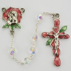The design theme for this rosary is the rose petal. The centerpiece is in the shape of a rose with an enamel background and a Madonna and Child centerpiece. The beads are clear aurora glass and shimmer in the light. The crucifix is like none other with rose petals comprising of the cross in red enamel and green leaves at the top. The Length is 22 inches Crucifix Measurement 2.07 x 1.11 x 0.24 inches Crucifix Material is Pewter Centerpiece Measurement 1.07 x 0.90 x 0.16 inches Centerpiece…
