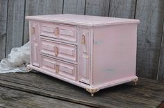 Upcycled vintage jewelry and music box. Wood, hand painted in soft pink, lightly distressed, and finally hand waxed. There are 3 drawers and 2 drop down ring holders. The music box plays a waltz when the lower drawer is opened. The drawer pulls and French provincial claw feet are painted pink and accented in gold. The interior is lined with gold colored velveteen. The perfect gift for her!  12.25 wide, 6.75 tall and 6.3 deep  All orders placed before 5 p.m. EST will ship the next business…