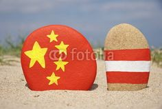 China and Austria's flags on stones with sand background