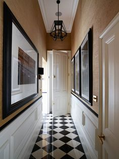 Black-and-white checkerboard flooring sets an elegant tone in the hallway | archdigest.com