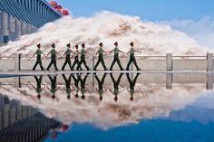 REFLECTIONS: Police patrolled along the Three Gorges Dam on the Yangtze River in China Tuesday. The hydroelectric dam experienced its largest flood peak this year on Tuesday after recent floods. (Xiao Yijiu/Xinhua/Zuma Press)