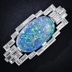 Art Deco black opal and diamond brooch. A glorious glowing black opal, displaying an entrancing palette of colors with the emphasis on blue, green and yellow, is elegantly presented in a geometric platinum frame containing thirty straight baguette diamonds totaling 4.00 carats. The surface of the opal displays mild crazing or checking. This unique and majestic Art Deco brooch measures 1 3/4 inches by 13/16 inch.
