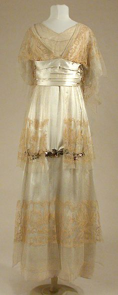 Afternoon gown, House of Paquin, 1912.  Silk underskirt overlaid with three tiers of Alencon lace, appliquéd with garland of silk rosebuds on the front of the skirt. Lace bodice extends to cape at the back.