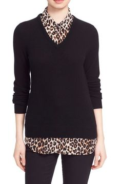 black v-neck sweater layered over leopard print button-down shirt