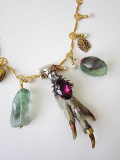 Taxidermy necklace. Victorian or gothic style jewellery with a medieval looking gold plated chain and an antique silver grouse foot at the centre. Big chunky pieces of rainbow fluorite hang either side along with a heart locket and an ace of spades card charm. by lux  and love.