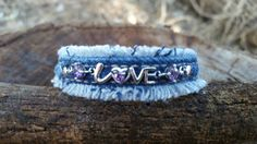 This is a frayed denim bracelet. The denim surrounds a silver LOVE bracelet with purple stones. This bracelet is small. It does have some chain for extention but would work best on a small wrist.