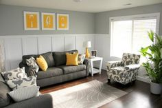 charcoal grey sofa and chair, yellow pillows and art pieces