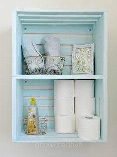 Blue Wooden Crate Storage- create bathroom storage with wooden crates hung on the wall as shelves.