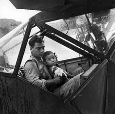 An American soldier tenderly holds a wounded Japanese boy inside an airplane as they await a flight to the nearest field hospital. The boy was wounded during the Allies' campaign to retake Saipan (of the Mariana Islands) and discovered by this soldier.