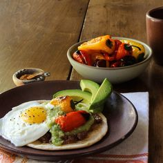 Huevos Rancheros - fried eggs top tortillas covered with refried beans, salsa and roasted sweet peppers.