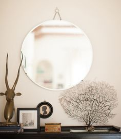 "Sneak Peek: Nicole Sutton of Workhorse. ""Another flea market treasure, this round mirror added just the right backdrop for the trinkets on top of an old cabinet I purchased from a moving sale downtown. The fan coral, brass springbok bust and framed silhouette are also second-hand finds and the ""golden twins"" tin was given to me by my mom. How apt!"" #sneakpeek"