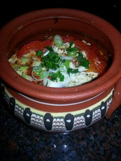 Bulgarian Gyuvetche: Cooked in a clay pot;  tomatoes, feta, sudjuk and roasted red peppers are layered then drizzled with olive oil and finished with an egg and green onions. #Bulgaria #Bulgarian