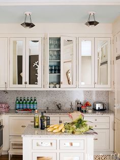 Antiqued mirrored glass on cabinet doors enlarges the small kitchen. Design: Jonathan Berger