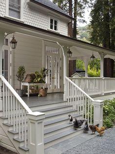White Farmhouse - Wraparound Porch with Hanging Lanterns
