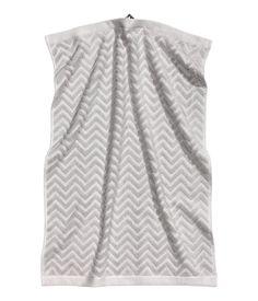 Ljusgrå. En handduk i bomullsfrotté med jacquardvävt sicksackmönster. Hängare på kortsidorna.