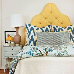 yellow upholstered bed with navy ikat pillows