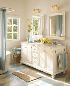 A soft palette of blue, sand and white brings a relaxed charm to this cottage-style bath. The floor tiles are arranged in oversized diamonds that create a sense of movement. Striped towels echo their color scheme, and the white vanity stands out against parchment-hued walls. Benjamin Moore™ Paint Color: OC-59 vanilla milkshake