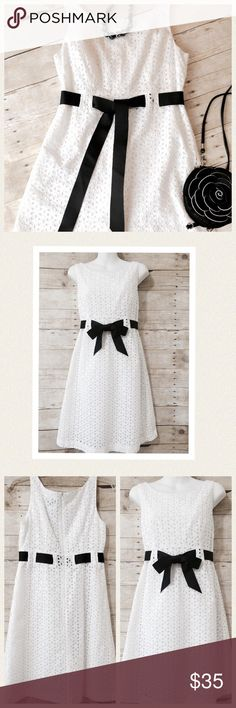 """Classic, chic white dress with black tie Stay cool and be fashionable in this eyelet cotton dress; perfect for those lovely summer luncheons. Classic style and design with interwoven black ribbon at base of bodice. Fully lined and zips in back Perfect condition Bust is 18"""" in front armpit to armpit Bodice length is 12.5"""" Waist is 33"""" Hips 36"""" Dress length 36.5"""" Sheri Martin Dresses"""