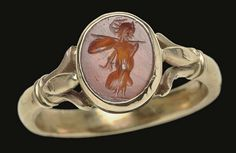 A ROMAN CARNELIAN RINGSTONE   CIRCA 2ND CENTURY A.D.   The flat oval stone with a striding Minerva, wearing a long peplos and crested helmet, shouldering a spear and shield; mounted as a ring in a modern gold setting