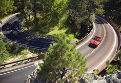 Red convertible driving on Iron Mountain Road, Black Hills, S.D. (© Visions of America/SuperStock)