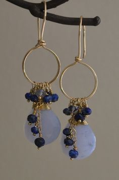 These lovely earrings feature blue lace agate gems topped with cascading clusters of lapis lazuli and Iolite rondelles. They are suspended from hand forged 14k gold filled hoops. These earrings are perfect for casual daytime wear or classic evening look. Earrings are 2 inches