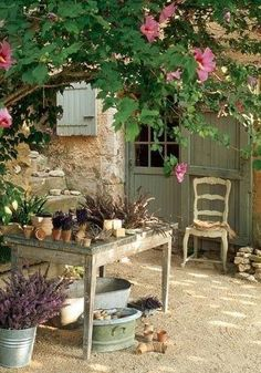 table under the shade of a tree in this lovely French cottage garden.