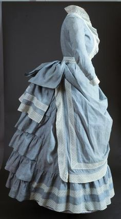 "~YOUNG LADY'S SEA SIDE ENSEMBLE, c. 1880 3-piece, skirt, bodice & belt, all in blue chambray trimmed w/ ivory eyelet bands: skirt w/ apron front, hem ruffle & 5 ruffles over bustle back; fitted blouse, front thread woven buttons, band collar; eyelet belt w/ huge chambray back bow, B 30"", W 20"", Skirt L 52"", (couple tiny holes, brown discoloration on chambray) very good; t/w 1 red & white striped cotton shirt waist, excellent. Brooklyn Museum~"