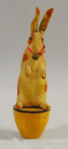 DISCOVERY   STUDIO PAINTINGS - SALE 2620M - LOT 523 - LATE 19TH CENTURY PAINTED STUFFED VELVET TOY RABBIT FIGURE ON TURNED WOOD BASE, WITH BELL AND GLASS EYES, HT. 9 1/4 IN. - Skinner Inc