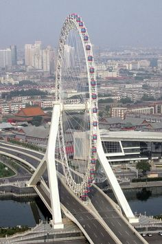 Tianjin Eye is a tall giant Ferris wheel built above the Yongle Bridge, over the Hai River in Tianjin, China. It is claimed to be the only such wheel to have been constructed over a bridge. Tianjin, Amazing Buildings, Amazing Architecture, Bridge Design, China Travel, Covered Bridges, Civil Engineering, Places To See, Beautiful Places