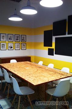LETTER FOUR's conference room with OSB table, Eames shell chairs, yellow striped walls, blackboards, and vintage flashcards.