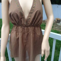 Open-Back Embellished Halter Top Brown Halter Top w/Embellishment at V-Neck. Elastic at Bodice. With a flared Bottom. Bottom. Bust area is lined! Very Cute Must Have Express Tops