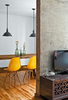 concrete half-wall, marigold Eames to pull out the gold tones in the wood, overhead pendant lights, antique media case.
