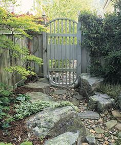 With the addition of some flat stepping stones, this streambed doubles as a garden path. The see-through, flow-through gate handles rising water while securing the backyard.