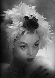 Model wearing a feathered hat for L'Officiel, December 1958.